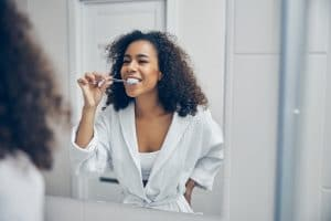 Cheerful young woman with a toothbrush in her hand looking at herself in the mirror